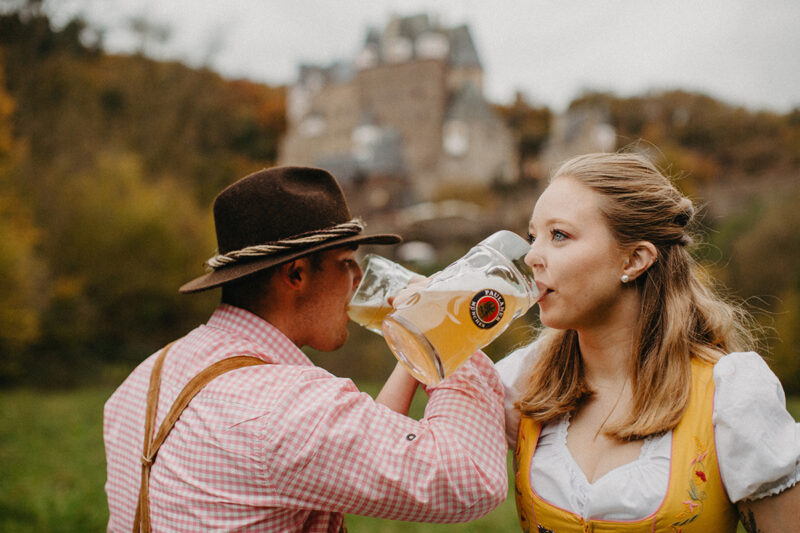 A couple drink together with mugs in a field near Burg Eltz wearing a traditional dirndl and lederhosen for these Eltz Castle couples photos in Germany