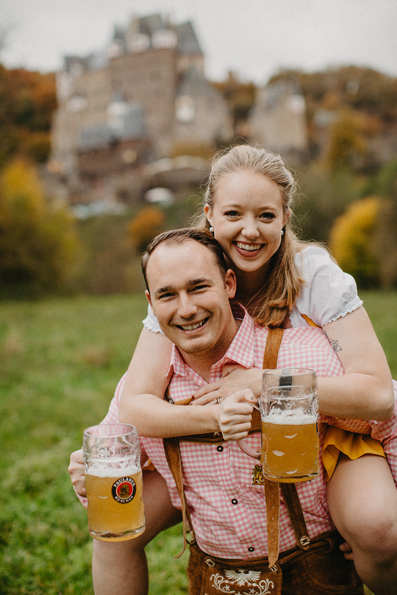 A couple embrace as he gives her a piggyback ride with beers in a field near Burg Eltz wearing a traditional dirndl and lederhosen for these Eltz Castle couples photos in Germany