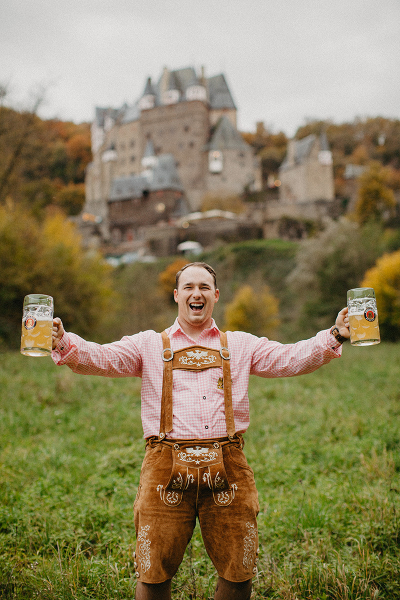 A handsome young man holds beer in a field near Burg Eltz wearing traditional lederhosen for these Eltz Castle couples photos in Germany