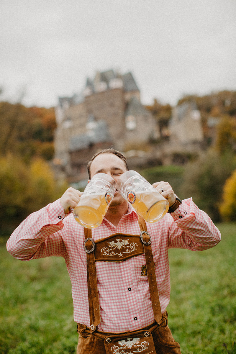 A handsome young man drinks beer in a field near Burg Eltz wearing traditional lederhosen for these Eltz Castle couples photos in Germany
