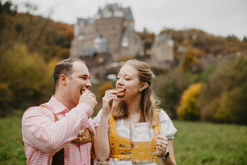A couple eat pretzels together with mugs of beer in a field near Burg Eltz wearing a traditional dirndl and lederhosen for these Eltz Castle couples photos in Germany