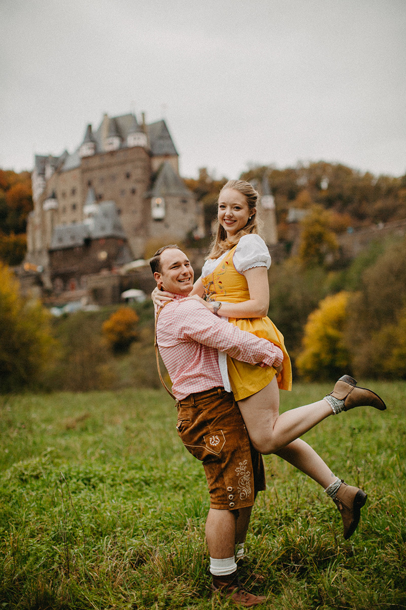 A couple embraces as he lifts her up in a field near Burg Eltz wearing a traditional dirndl and lederhosen for these Eltz Castle couples photos in Germany