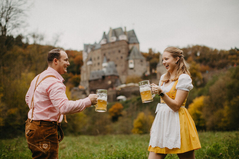 A couple cheers with mugs in a field near Burg Eltz wearing a traditional dirndl and lederhosen for these Eltz Castle couples photos in Germany