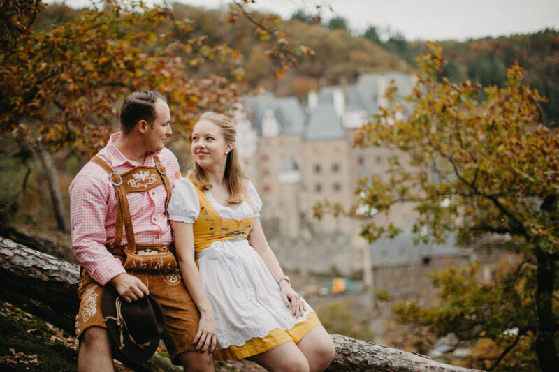 A couple embrace as they sit near Burg Eltz wearing a traditional dirndl and lederhosen for these Eltz Castle couples photos in Germany