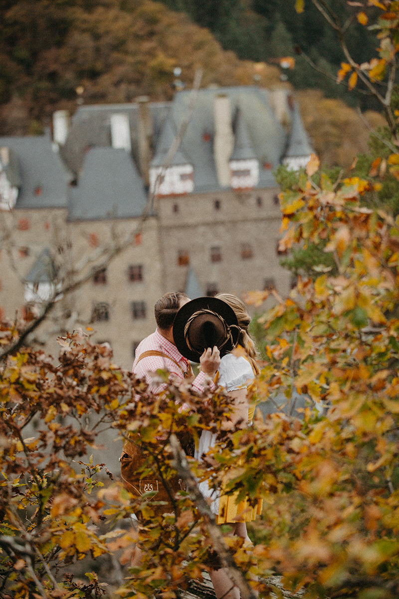 A couple embrace and kiss behind a hat near Burg Eltz wearing a traditional dirndl and lederhosen for these Eltz Castle couples photos in Germany