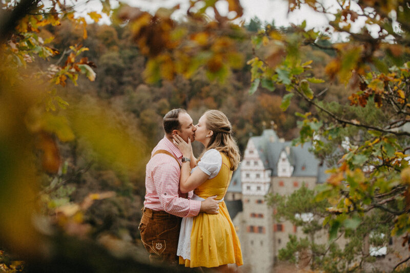 A couple embrace and kiss near Burg Eltz wearing a traditional dirndl and lederhosen for these Eltz Castle couples photos in Germany