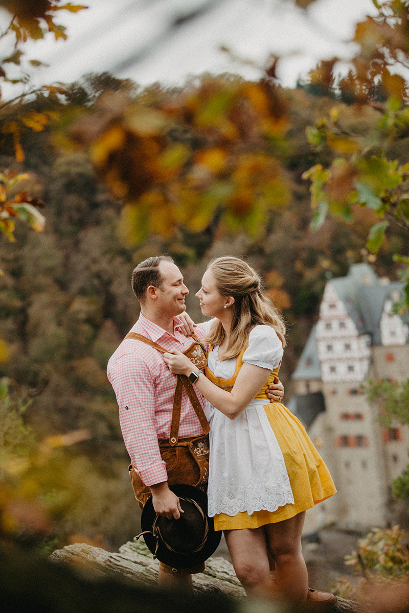 A couple embrace near Burg Eltz wearing a traditional dirndl and lederhosen for these Eltz Castle couples photos in Germany