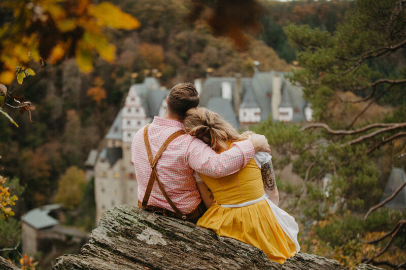 A couple embrace sitting on a ridge near Burg Eltz wearing a traditional dirndl and lederhosen for these Eltz Castle couples photos in Germany