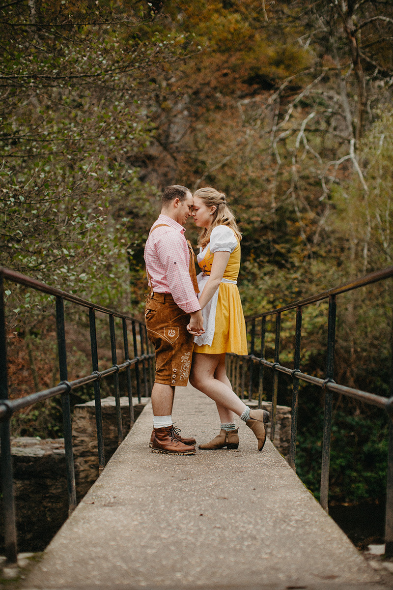 A couple embraces on a bridge near Burg Eltz wearing a traditional dirndl and lederhosen for these Eltz Castle couples photos in Germany