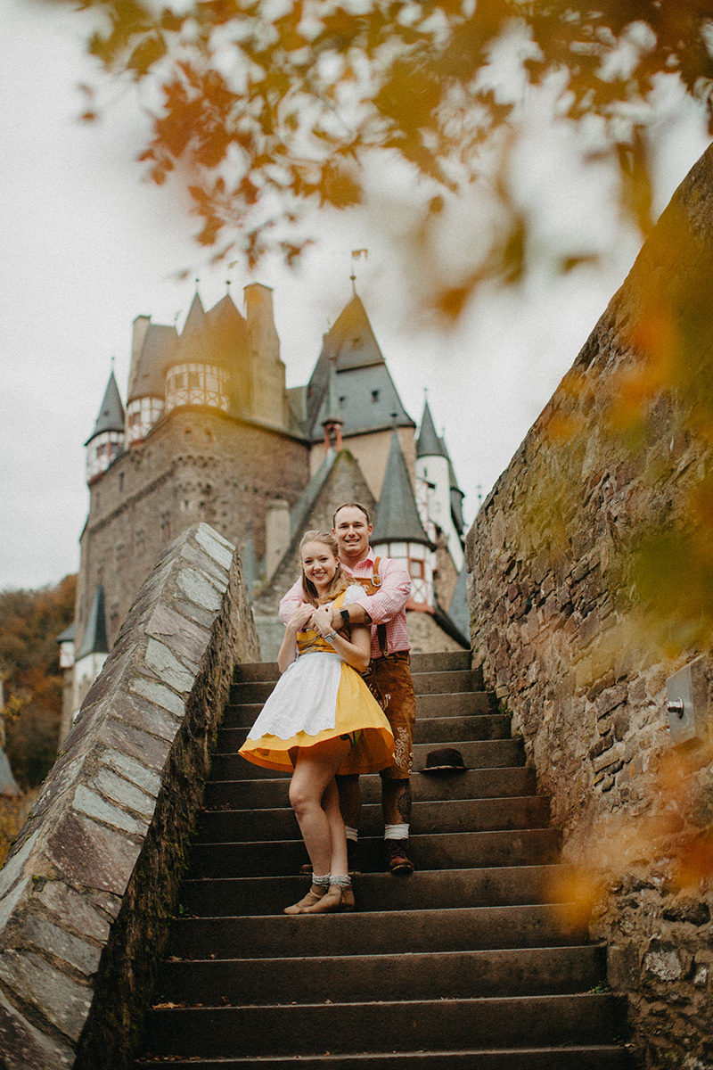 A couple embraces on stairs near Burg Eltz wearing a traditional dirndl and lederhosen for these Eltz Castle couples photos in Germany