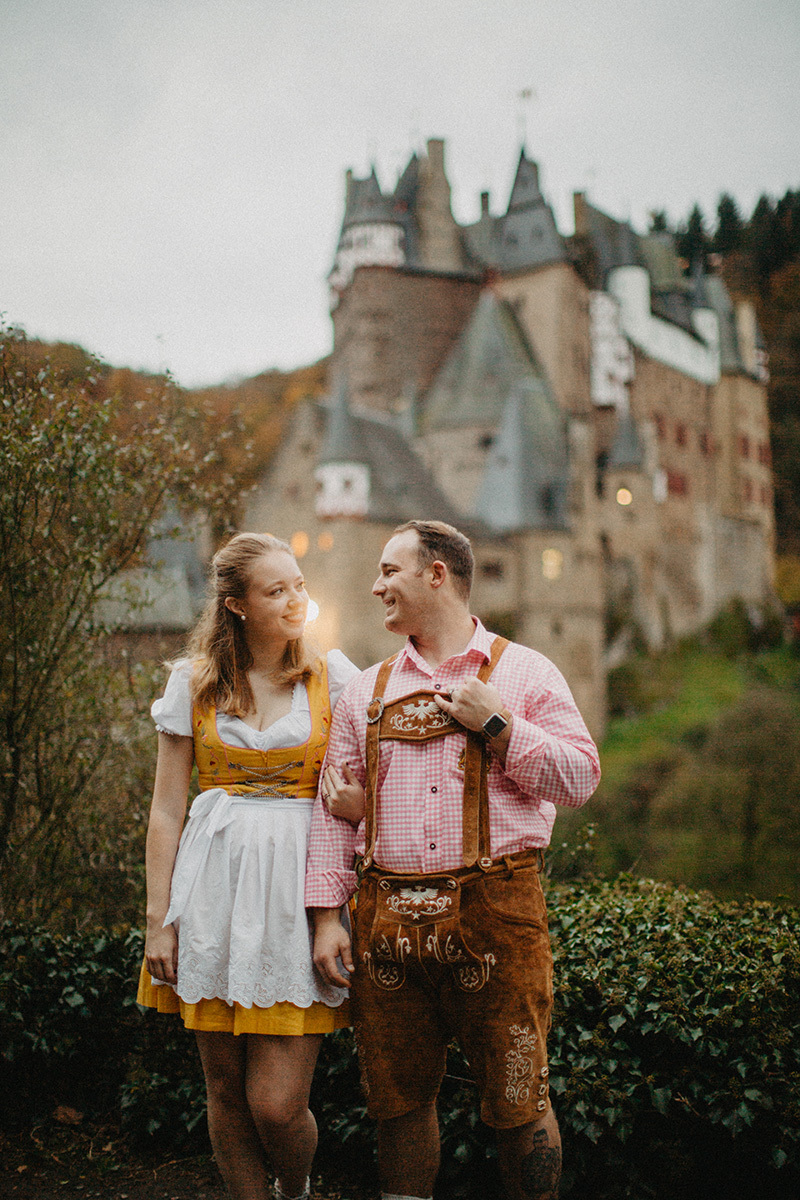 A couple holds hands in front of Burg Eltz wearing a traditional dirndl and lederhosen for these Eltz Castle couples photos in Germany