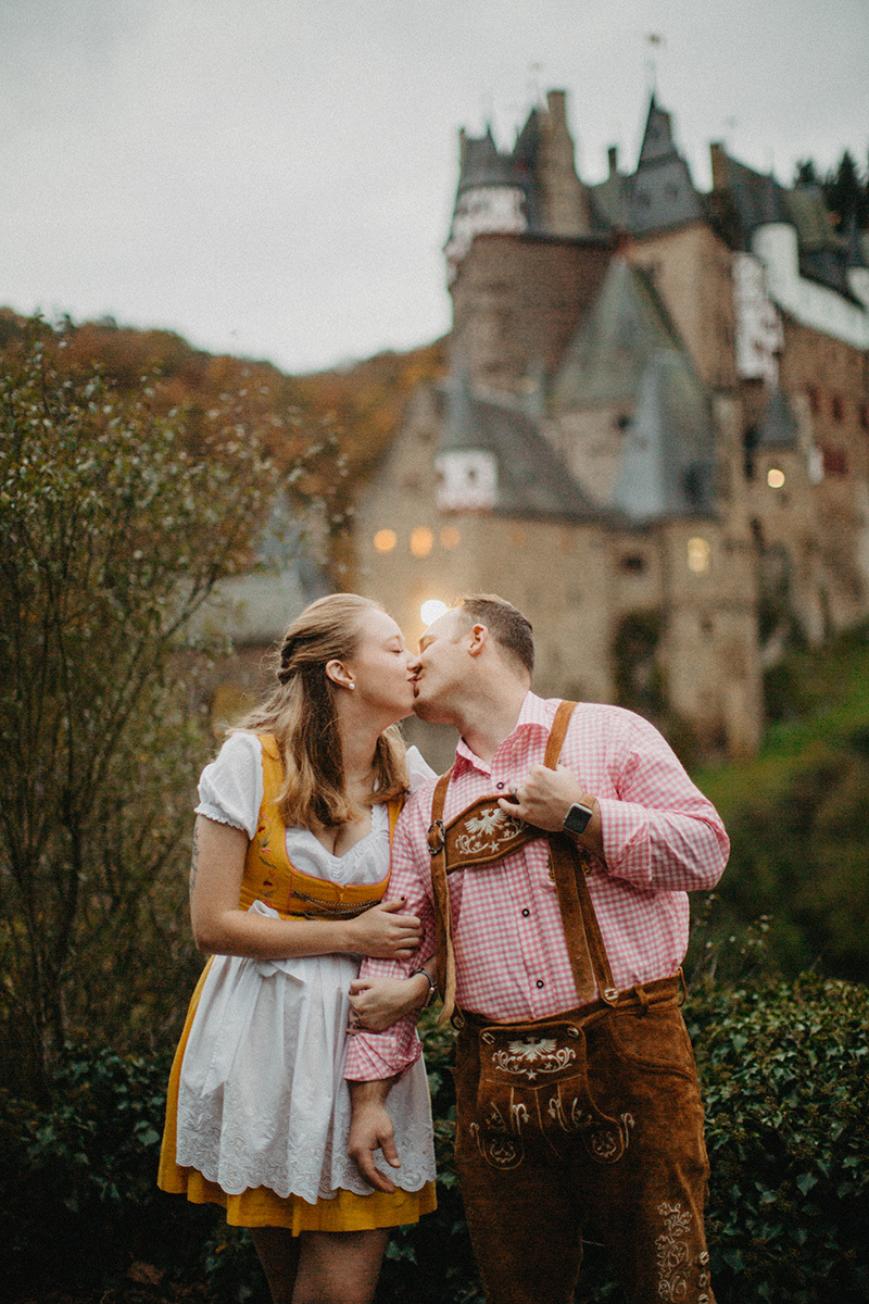 A couple holds hands and kiss in front of Burg Eltz wearing a traditional dirndl and lederhosen for these Eltz Castle couples photos in Germany