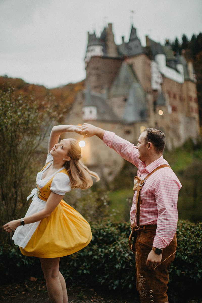 A couple dances in front of Burg Eltz wearing a traditional dirndl and lederhosen for these Eltz Castle couples photos in Germany