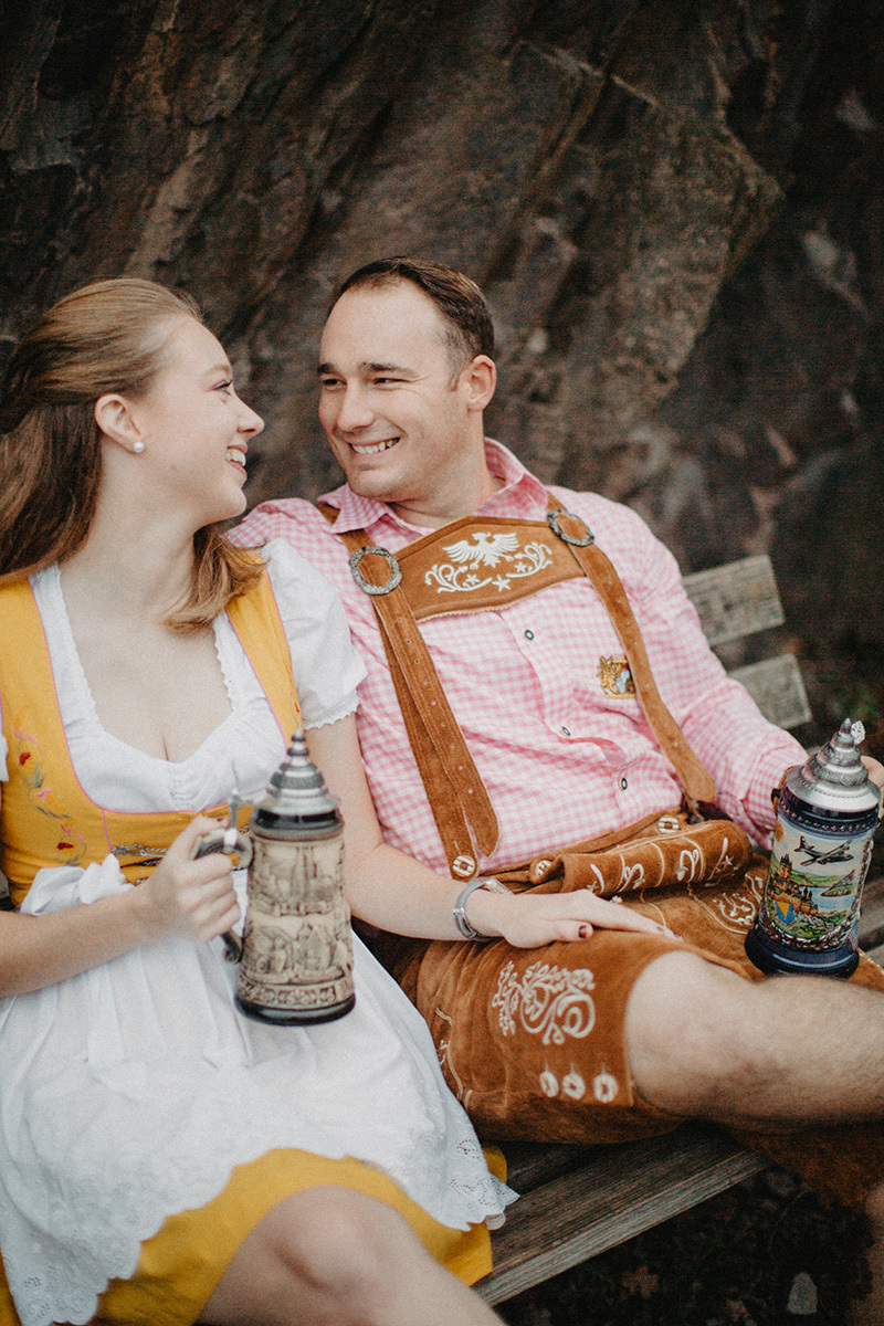 A couple embraces holding steins near Burg Eltz wearing a traditional dirndl and lederhosen for these Eltz Castle couples photos in Germany