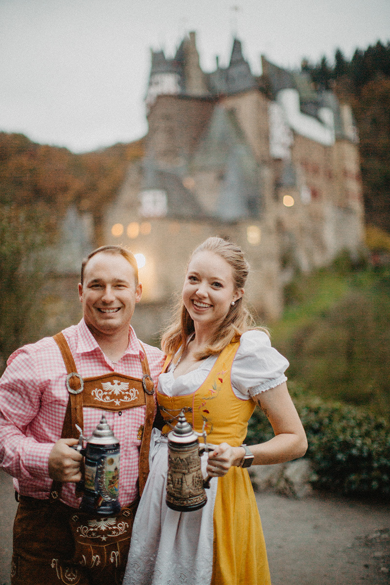 A couple embraces holding steins in front of Burg Eltz wearing a traditional dirndl and lederhosen for these Eltz Castle couples photos in Germany