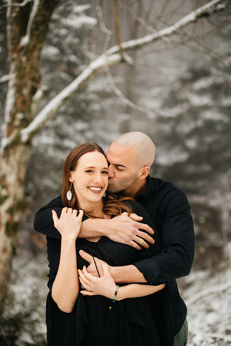A couple embrace in a snow covered forest in Germany wearing a beautiful black dress and black button up shirt for a Black Forest engagement photography session