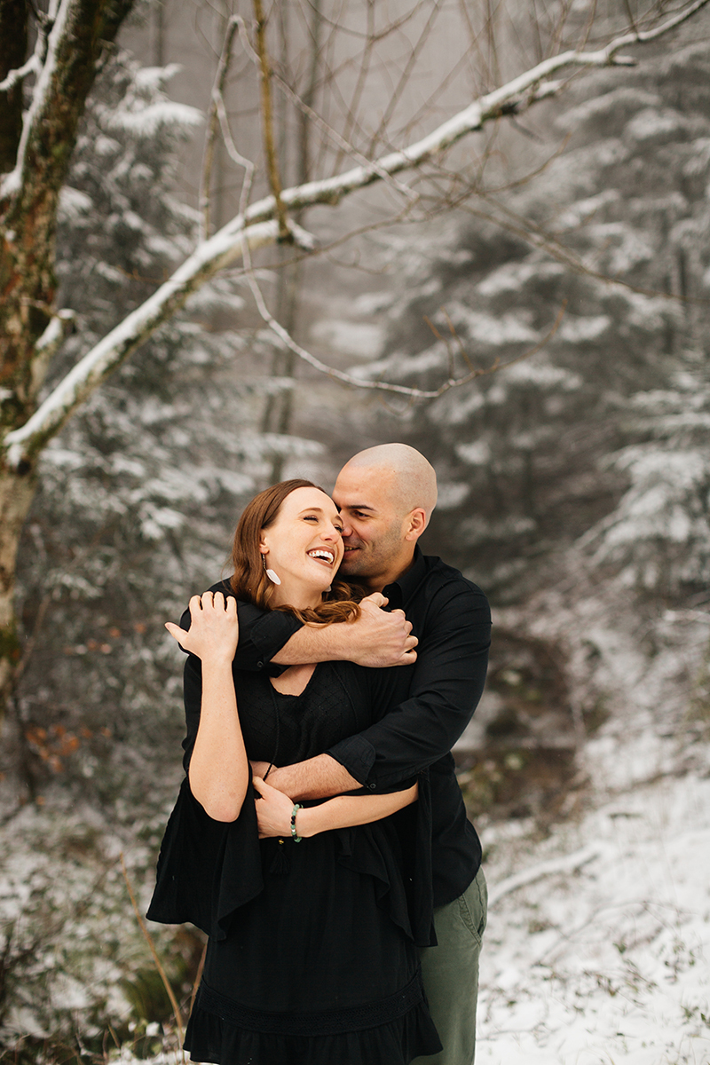 A couple embrace and laugh in a snow covered forest in Germany wearing a beautiful black dress and black button up shirt for a Black Forest engagement photography session