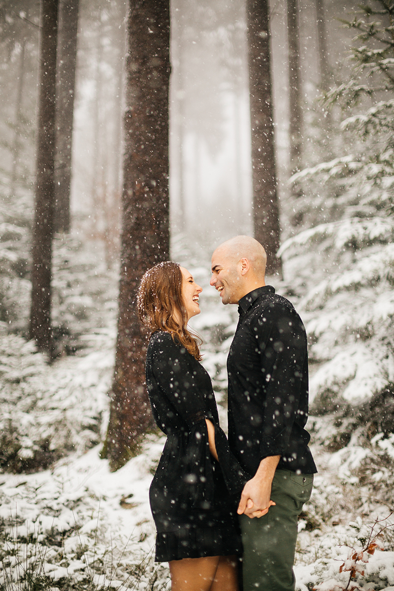 A couple hold hands in a snow covered forest in Germany wearing a beautiful black dress and black button up shirt for a Black Forest engagement photography session