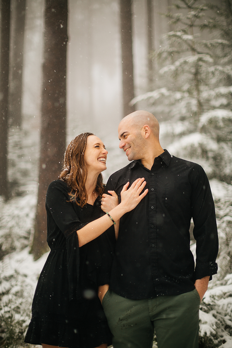 A couple stand side by side in a snow covered forest in Germany wearing a beautiful black dress and black button up shirt for a Black Forest engagement photography session