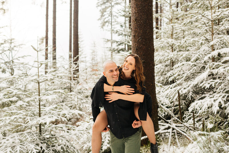 A couple embrace as he gives her a piggyback ride in a snow covered forest in Germany wearing a beautiful black dress and black button up shirt for a Black Forest engagement photography session