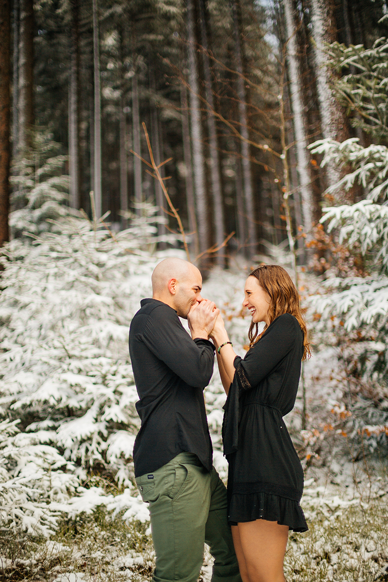A couple embrace as he warms her handds in a snow covered forest in Germany wearing a beautiful black dress and black button up shirt for a Black Forest engagement photography session
