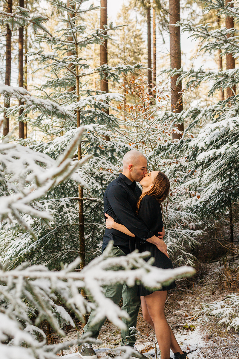 A couple embrace and kiss in a snow covered forest in Germany wearing a beautiful black dress and black button up shirt for a Black Forest engagement photography session