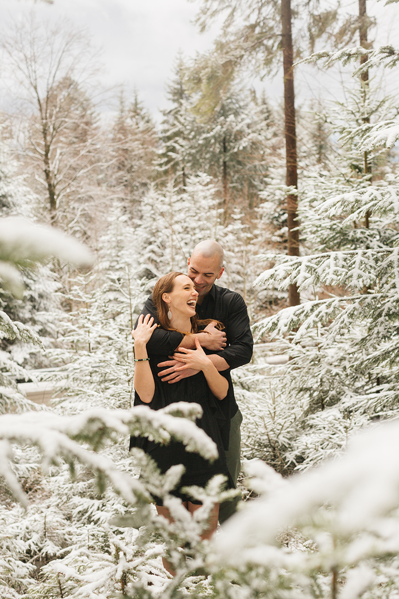 A couple embraces in a snow covered forest in Germany wearing a beautiful black dress and black button up shirt for a Black Forest engagement photography session