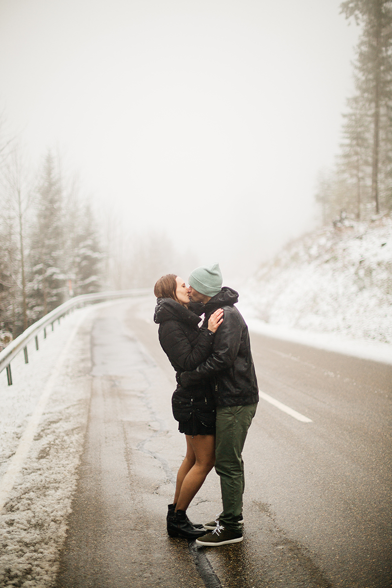 A couple embraces on a road through a snow covered forest in Germany wearing a beautiful black dress and black button up shirt for a Black Forest engagement photography session