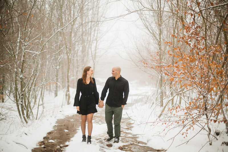 A couple holds hands as they walk in a snow covered forest in Germany wearing a beautiful black dress and black button up shirt for a Black Forest engagement photography session