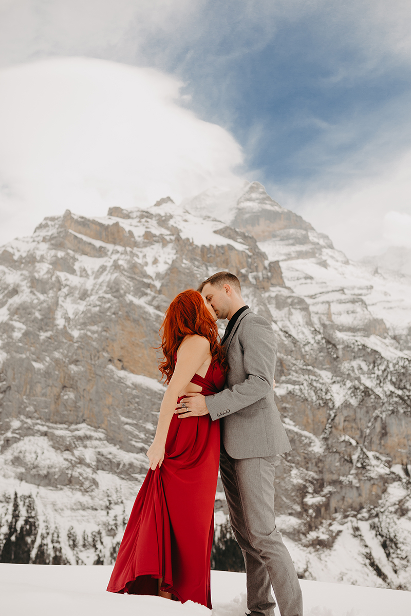 A couple kiss on a snow covered mountain in Switzerland wearing a beautiful red dress and gray suit for a Mürren couples photography session