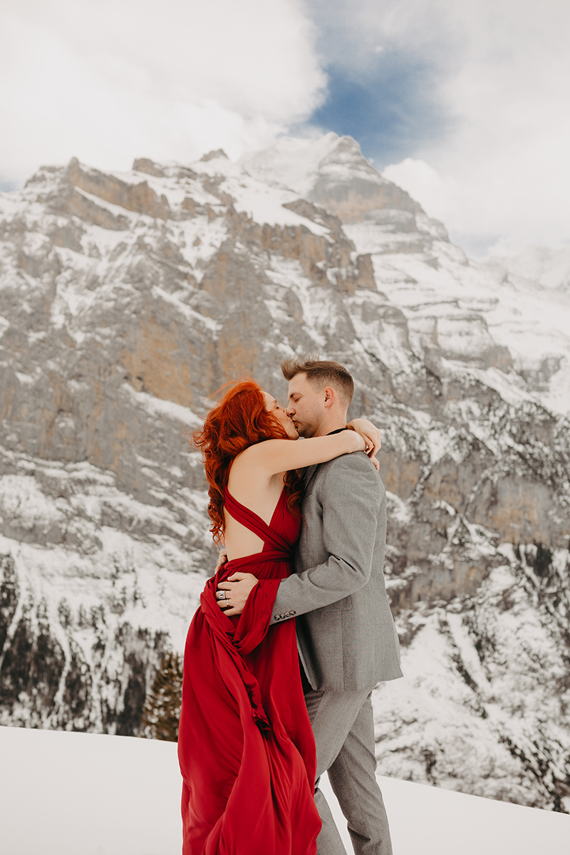 A couple embrace and kiss on a snow covered mountain in Switzerland wearing a beautiful red dress and gray suit for a Mürren couples photography session