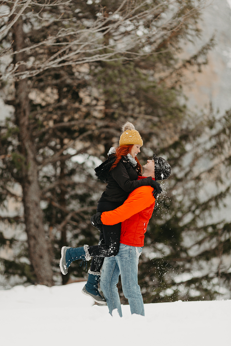 A couple embrace and kiss as he lifts her up in trees on a snow covered mountain in Switzerland wearing snow gear for a Mürren couples photography session