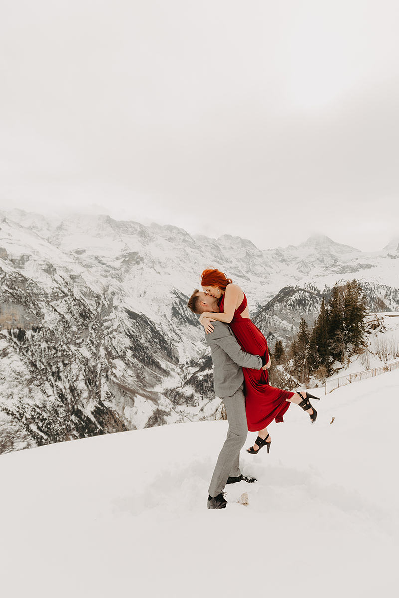 A couple embrace and kiss as he lifts her up on a snow covered mountain in Switzerland wearing a beautiful red dress and gray suit for a Mürren couples photography session