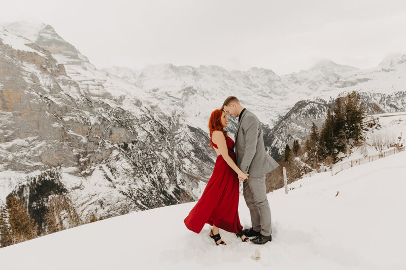 A couple embrace on a snow covered mountain in Switzerland wearing a beautiful red dress and gray suit for a Mürren couples photography session
