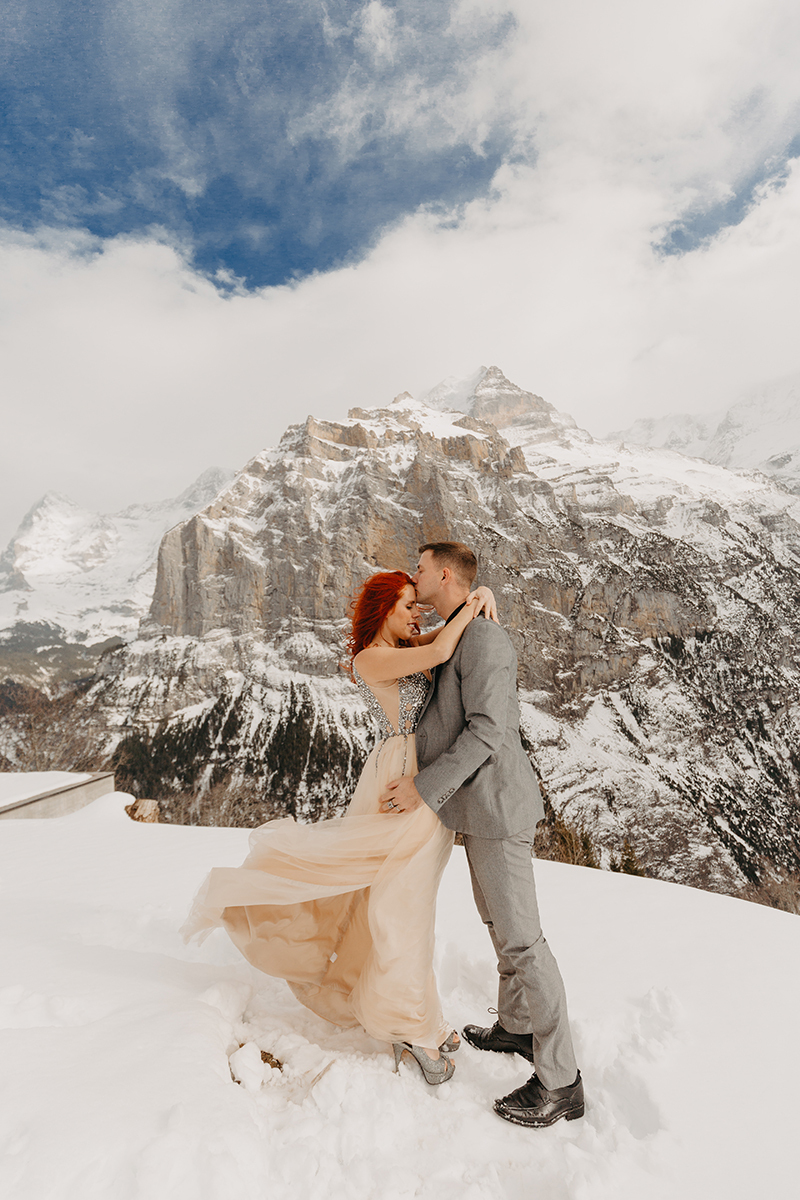 A couple embraces on a snow covered mountain in Switzerland wearing a beautiful peach colored dress and gray suit for a Mürren couples photography session
