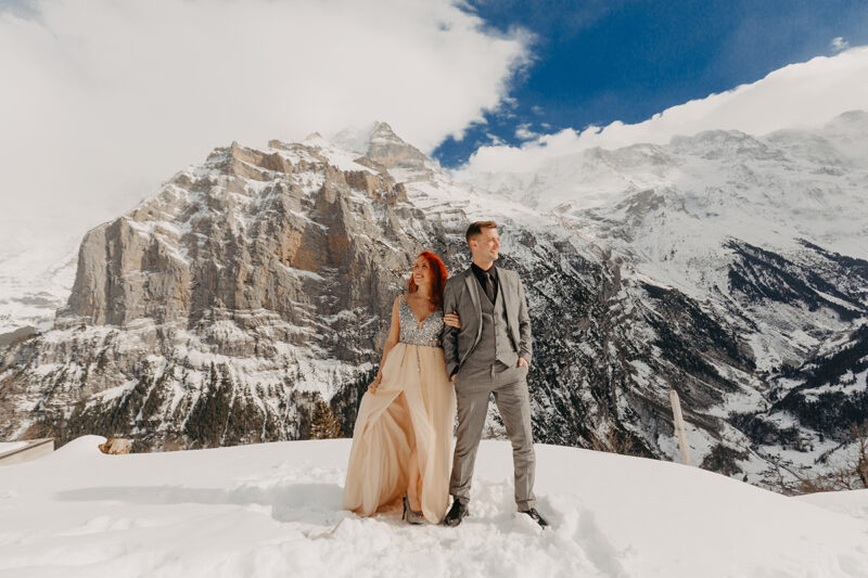 A couple stands side by side on a snow covered mountain in Switzerland wearing a beautiful peach colored dress and gray suit for a Mürren couples photography session