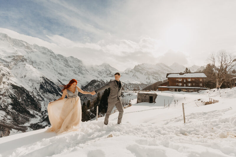 A couple holds hands walking up a snow covered mountain in Switzerland wearing a beautiful peach colored dress and gray suit for a Mürren couples photography session