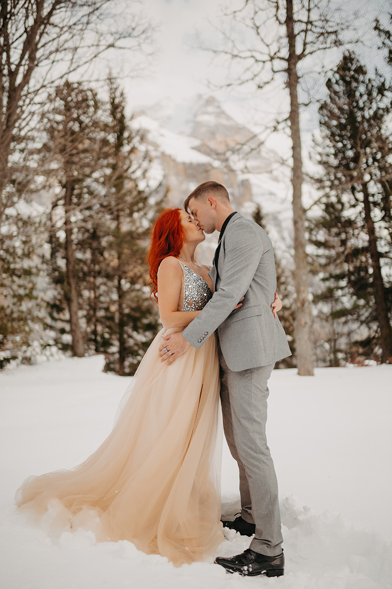 A couple embrace and kiss in trees on a snow covered mountain in Switzerland wearing a beautiful peach colored dress and gray suit for a Mürren couples photography session