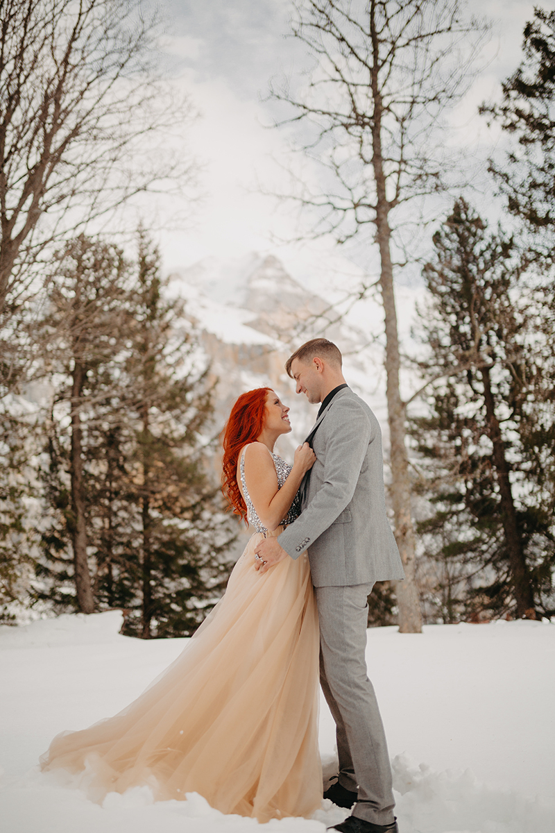 A couple embrace in trees on a snow covered mountain in Switzerland wearing a beautiful peach colored dress and gray suit for a Mürren couples photography session