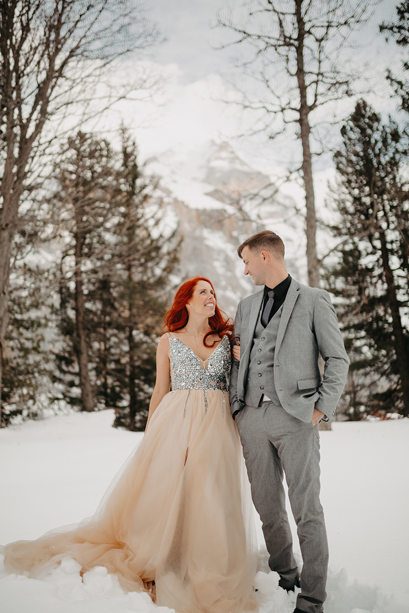 A couple walks side by side in trees on a snow covered mountain in Switzerland wearing a beautiful peach colored dress and gray suit for a Mürren couples photography session