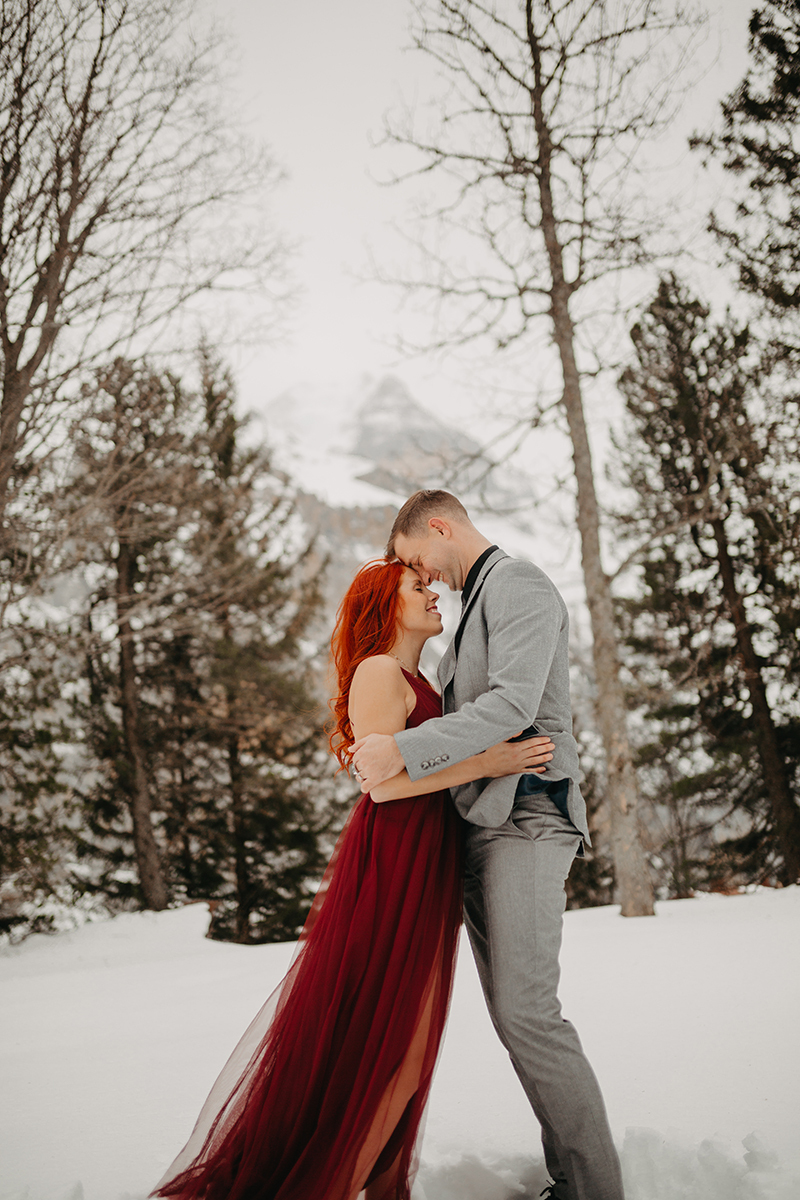A couple embraces in trees on a snow covered mountain in Switzerland wearing a beautiful red dress and gray suit for a Mürren couples photography session