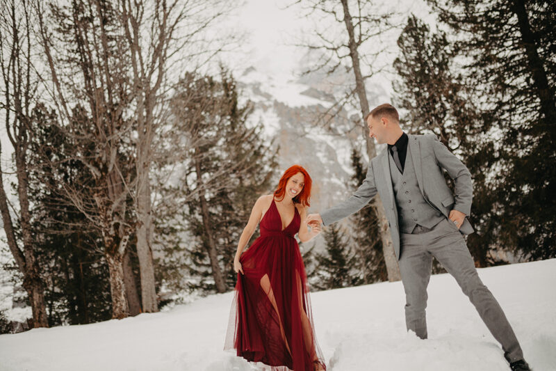 A couple walks holding hands in trees on a snow covered mountain in Switzerland wearing a beautiful red dress and gray suit for a Mürren couples photography session