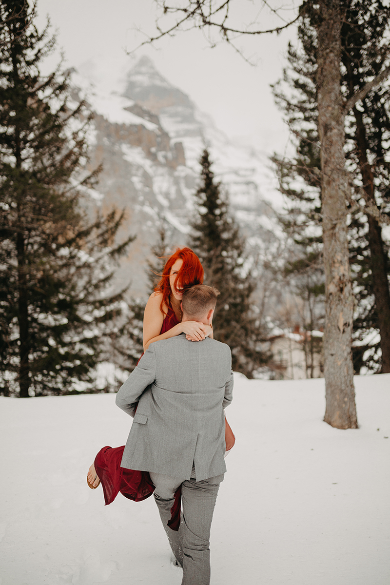 A couple walks as he carries her in trees on a snow covered mountain in Switzerland wearing a beautiful red dress and gray suit for a Mürren couples photography session