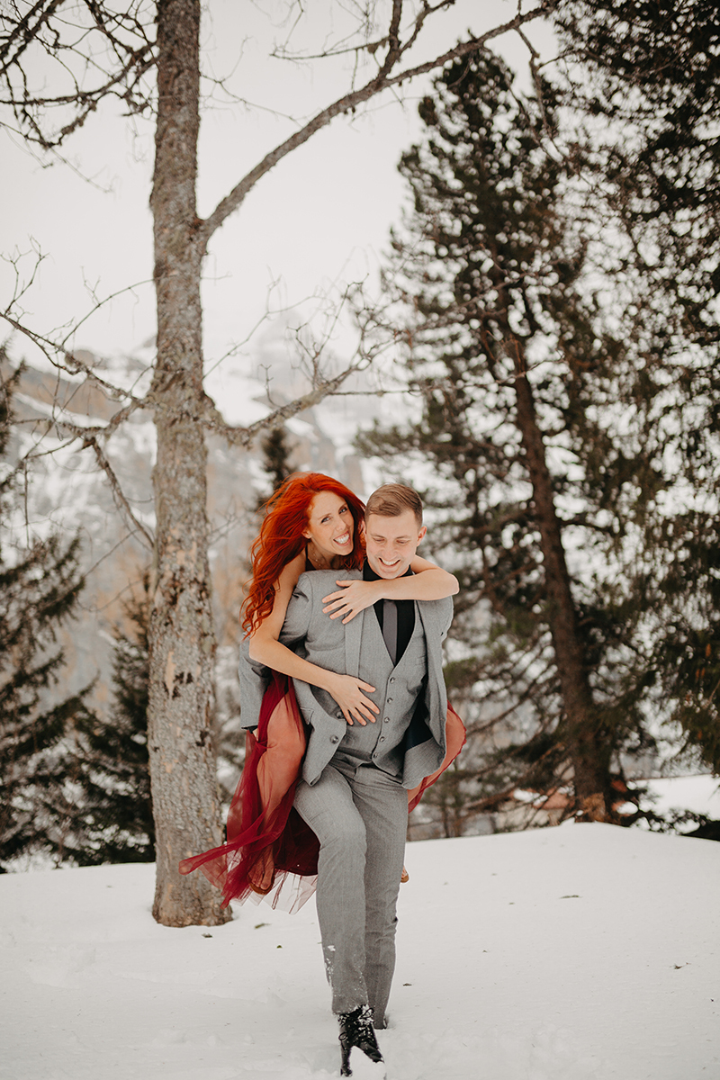 A couple walks as he gives her a piggyback ride in trees on a snow covered mountain in Switzerland wearing a beautiful red dress and gray suit for a Mürren couples photography session