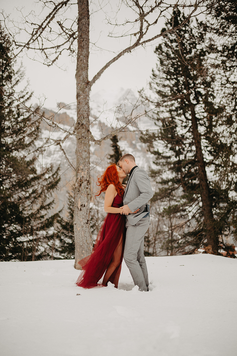 A couple embrace and kiss in trees on a snow covered mountain in Switzerland wearing a beautiful red dress and gray suit for a Mürren couples photography session