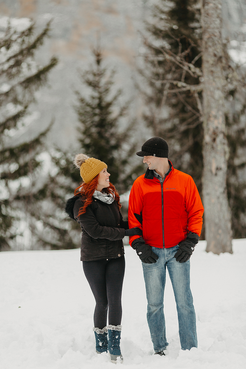 A couple walks together in trees on a snow covered mountain in Switzerland wearing snow gear for a Mürren couples photography session