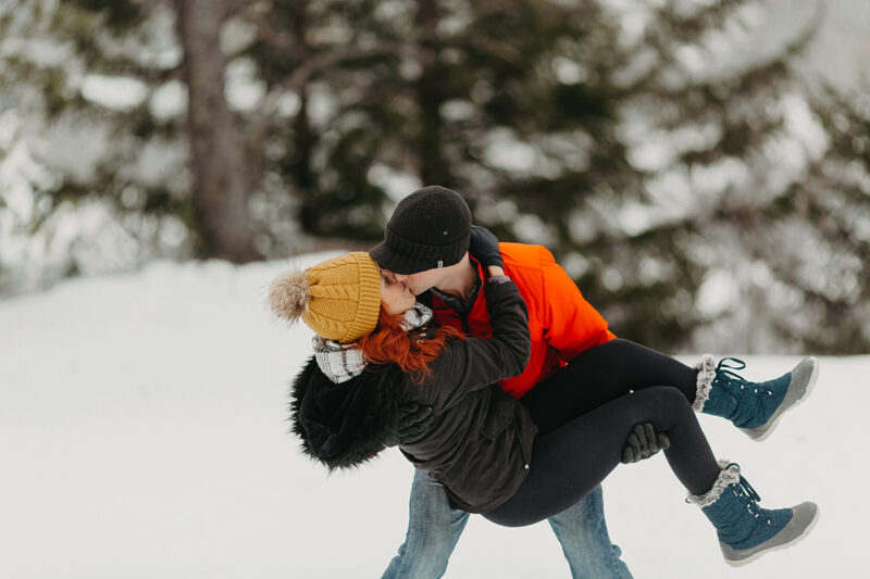A couple embraces in trees on a snow covered mountain in Switzerland wearing snow gear for a Mürren couples photography session