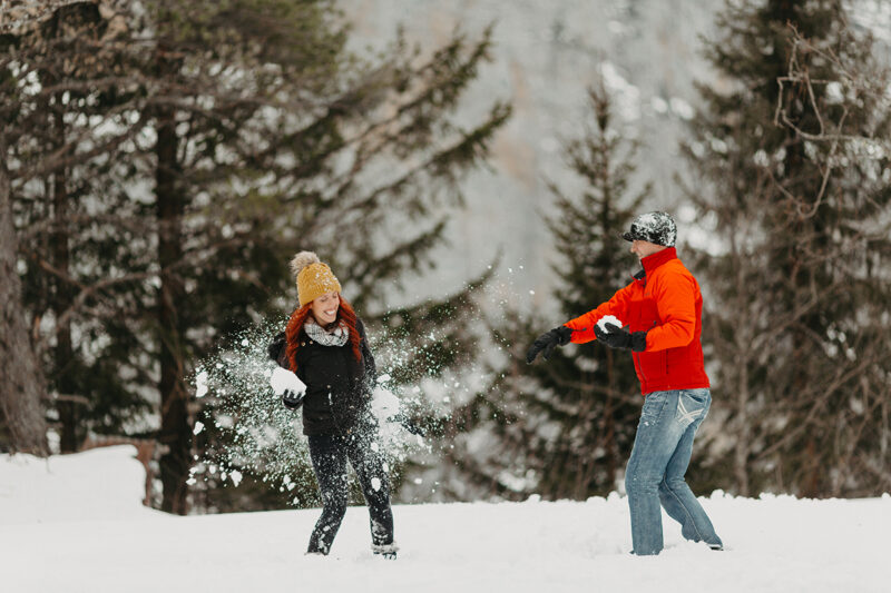 A couple having a snowball fight in trees on a snow covered mountain in Switzerland wearing snow gear for a Mürren couples photography session