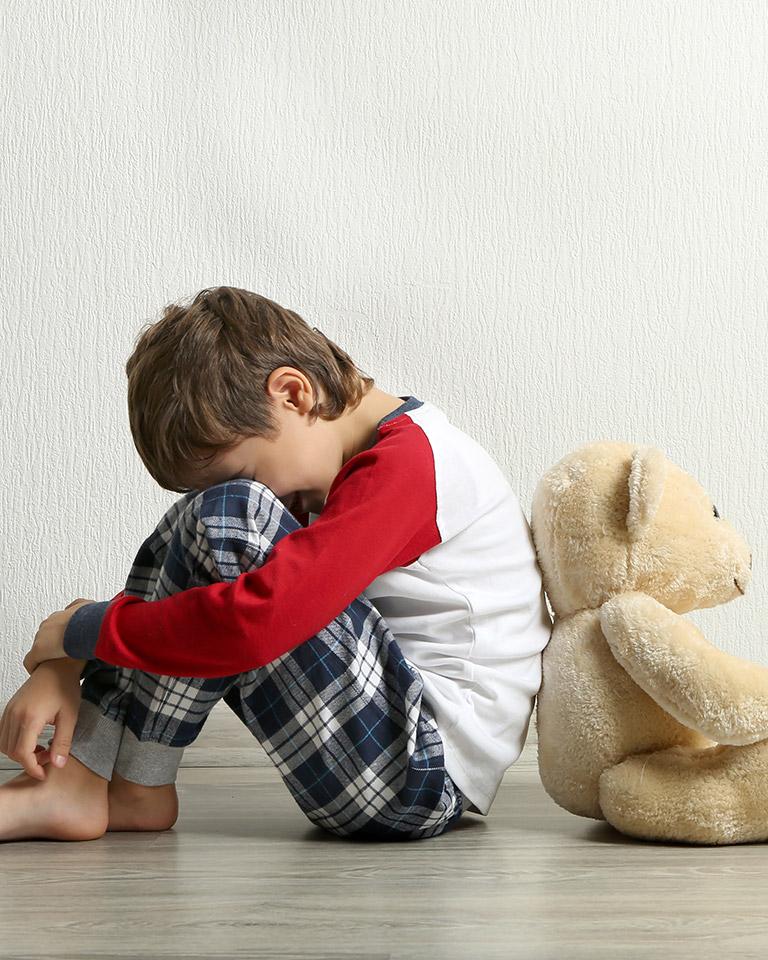 sad little boy hiding face with teaddy bear