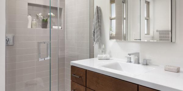 Renovated bathroom with clear shower door open in front of wooden cabinet sink